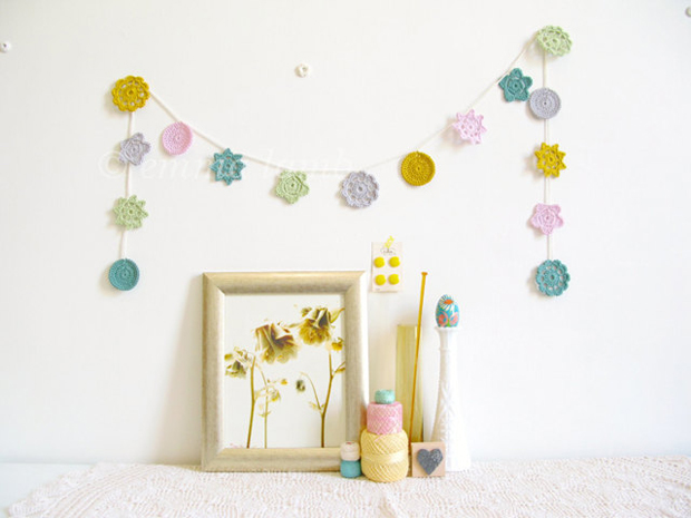 Crochet garland hanged on the wall in Spring pastel colours by Emma Lamb