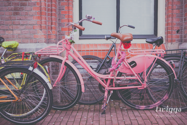 A pink bike parked outside in Amsterdam by Twiggs Photography