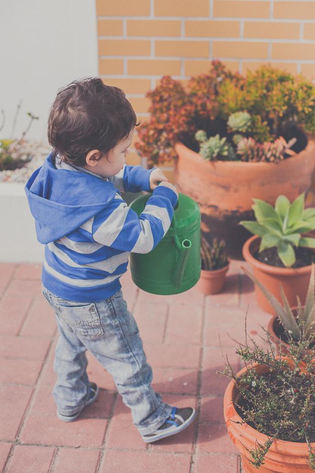 Criança a brincar no jardim com regador