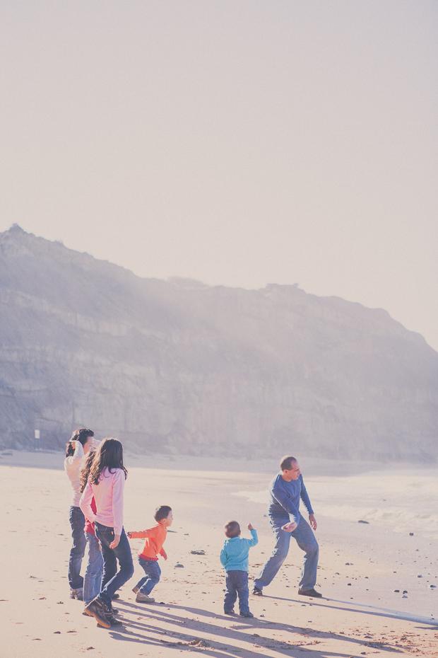 Família a brincar à beira mar