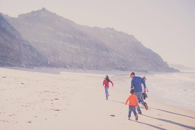 Família a correr pela praia