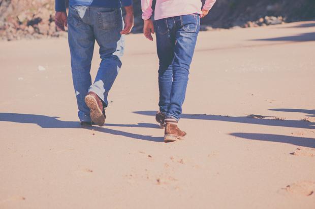 Pai e filha a caminhar na praia