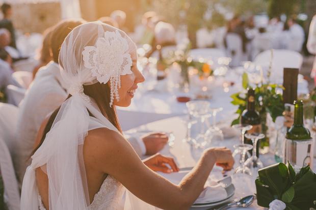 Fotografia de Casamento - Noiva sorri sentada à mesa ao pôr-do-sol