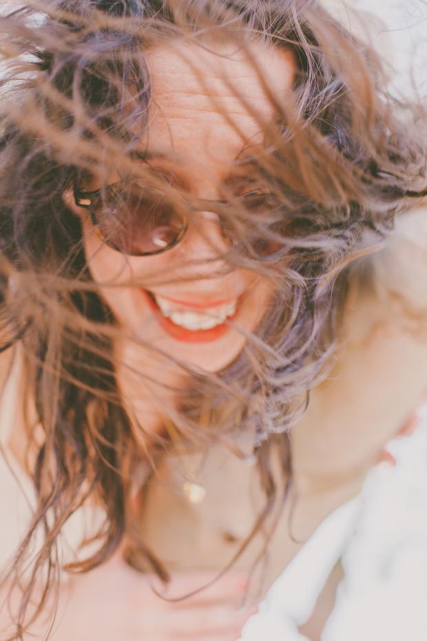Rapariga a sorrir de cabelos ao vento