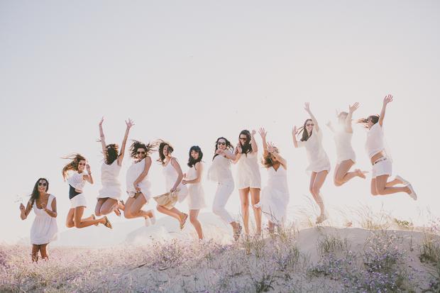 Grupo de raparigas vestidas de branco a saltarem