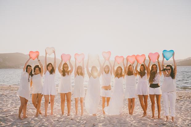 Raparigas alinhadas com balões na praia ao pôr-do-sol